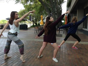 """[From the right] Seniors Taylor Thayer and Erica Lobel, along with junior Hannah Hilbelink practice their routine before performing """"Wolf Child"""" at the state competition."""