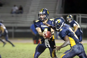 Quarterback Quentin Poteralski passes the ball off to Jayquese Dantley. Dantley scored two touch downs for the Steinbrenner Warriors.