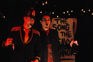 Nick P (Macheath) and Owen Dee (Sheriff Brown) sing the Song of Heavy Cannon, which is all about their time in the military.